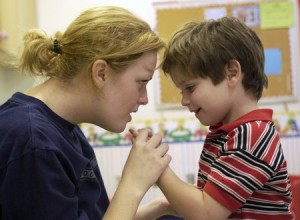 Autism research story. SIU students in Behavioral Analysis and Therapy and Communications Disorders work with children with autism problems in their laboratories. Only the names of the SIU students appear in the caption info. L to r: Kelli Tande, graduate student in Behavioral Analysis and Therapy, works with a four-year-old who doesn't speak. Using rewards that the child can choose (videos, snacks, etc.) they work on a repetitive pattern to develop the speech process.
